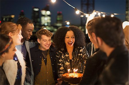 Young friends celebrating birthday at rooftop party Stock Photo - Premium Royalty-Free, Code: 6113-08568786