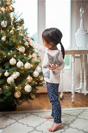 Toddler girl decorating Christmas tree Stock Photo - Premium Royalty-Free, Code: 6113-08521307