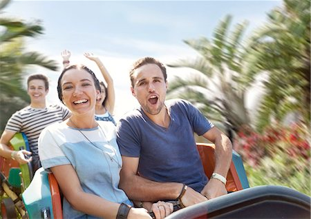 Young couple cheering on amusement park ride Stock Photo - Premium Royalty-Free, Code: 6113-08521310