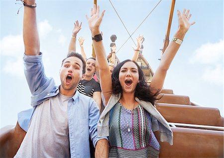 Portrait enthusiastic friends cheering on amusement park ride Stock Photo - Premium Royalty-Free, Code: 6113-08521333