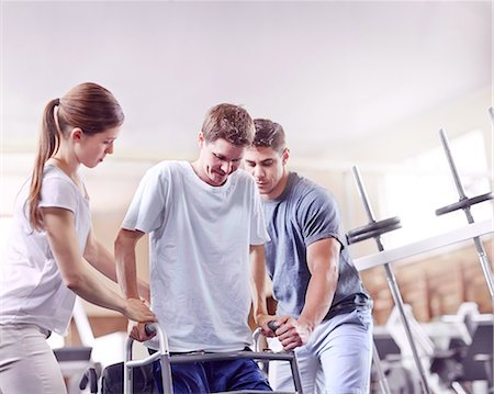 Physical therapists helping man with walker Stock Photo - Premium Royalty-Free, Code: 6113-08521461