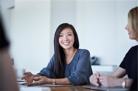 Smiling businesswoman in meeting Stock Photo - Premium Royalty-Free, Code: 6113-08521403