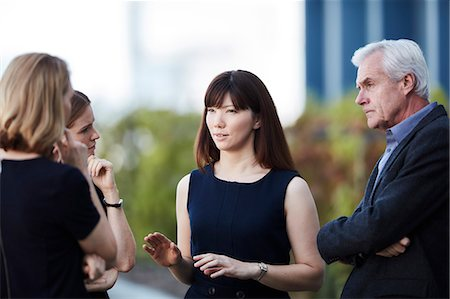 Businesswoman gesturing and talking to colleagues Stock Photo - Premium Royalty-Free, Code: 6113-08521430