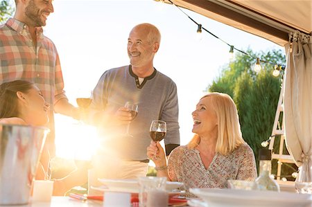 Family drinking wine at sunny patio table Stock Photo - Premium Royalty-Free, Code: 6113-08521556