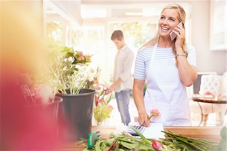 florist - Smiling florist talking on cell phone in flower shop Stock Photo - Premium Royalty-Free, Code: 6113-08536177