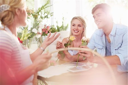 Florist discussing roses with couple in flower shop Stock Photo - Premium Royalty-Free, Code: 6113-08536188