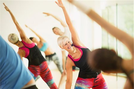 Smiling fitness instructor leading aerobics class stretching arms Stock Photo - Premium Royalty-Free, Code: 6113-08536124