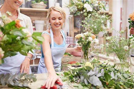 florist - Smiling florist arranging bouquet in flower shop Stock Photo - Premium Royalty-Free, Code: 6113-08536202