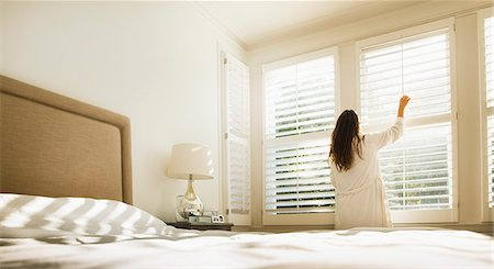 Woman in bathrobe opening bedroom window blinds Stock Photo - Premium Royalty-Free, Code: 6113-08655477