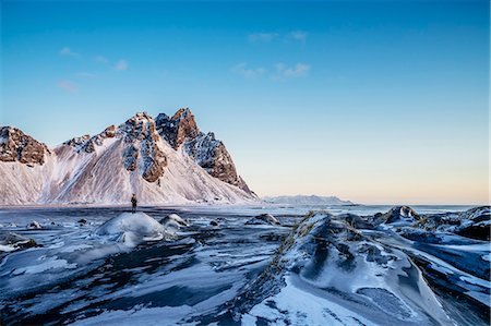 Woman standing among remote, icy landscape, Hofn, Iceland Stock Photo - Premium Royalty-Free, Code: 6113-08655494