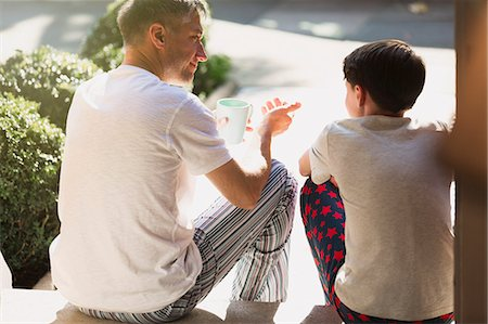 Father with coffee talking to son on front stoop Stock Photo - Premium Royalty-Free, Code: 6113-08655404