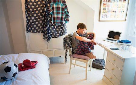 Bored boy doing homework at desk in bedroom Stock Photo - Premium Royalty-Free, Code: 6113-08655413