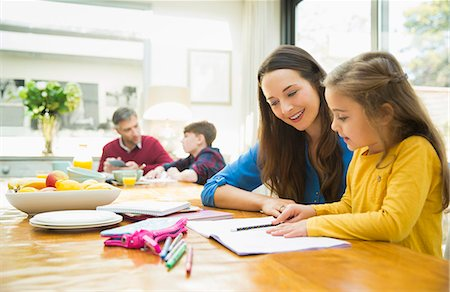 Mother and daughter doing homework at dining table Stock Photo - Premium Royalty-Free, Code: 6113-08655425