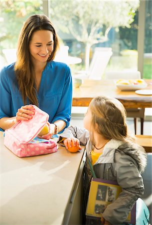 Mother packing lunch for daughter in kitchen Stock Photo - Premium Royalty-Free, Code: 6113-08655433