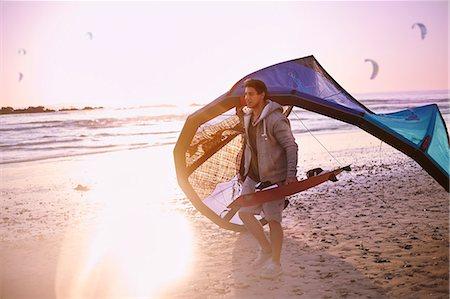 Man carrying kiteboarding equipment on sunset beach Stock Photo - Premium Royalty-Free, Code: 6113-08655570