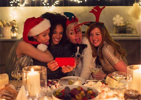 Playful young women with dog taking selfie at Christmas dinner Stock Photo - Premium Royalty-Free, Code: 6113-08659556