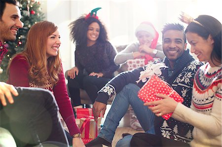 Friends opening Christmas gifts in living room Stock Photo - Premium Royalty-Free, Code: 6113-08659578
