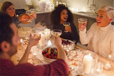Enthusiastic friends toasting champagne glasses at candlelight Christmas dinner Stock Photo - Premium Royalty-Free, Code: 6113-08659590