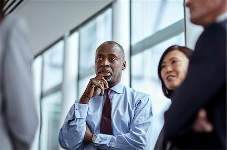 Attentive serious businessman listening to colleagues Stock Photo - Premium Royalty-Free, Code: 6113-08659668