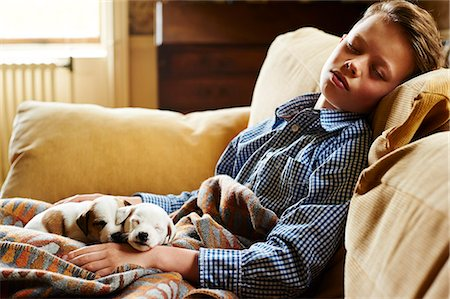 Boy and puppies sleeping on sofa Stock Photo - Premium Royalty-Free, Code: 6113-08659680