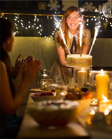 Enthusiastic woman serving cake with sparkler fireworks to clapping friends Stock Photo - Premium Royalty-Free, Code: 6113-08659613