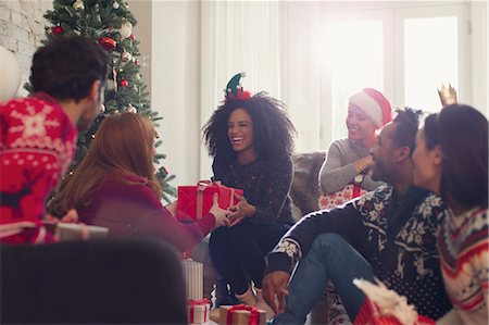 Smiling friends exchanging Christmas gifts in living room Stock Photo - Premium Royalty-Free, Code: 6113-08659616