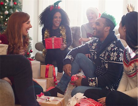 southeast asian ethnicity - Laughing friends opening Christmas gifts in living room Stock Photo - Premium Royalty-Free, Code: 6113-08659620