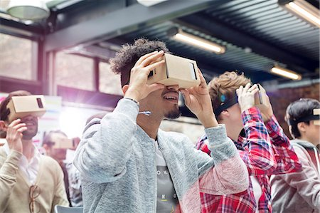 Audience trying virtual reality simulator glasses at technology conference Stock Photo - Premium Royalty-Free, Code: 6113-08698057
