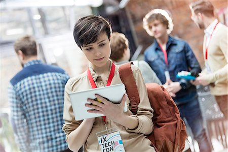 Young woman using digital tablet at technology conference Foto de stock - Sin royalties Premium, Código: 6113-08698013