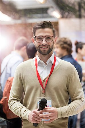 Portrait smiling speaker with microphone at technology conference Stock Photo - Premium Royalty-Free, Code: 6113-08698012