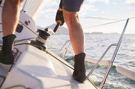 sailboat  ocean - Man sailing turning cable winch on heeling sailboat Stock Photo - Premium Royalty-Free, Code: 6113-08698143