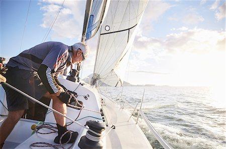 sailboat  ocean - Man sailing pulling rigging on sailboat on sunny ocean Stock Photo - Premium Royalty-Free, Code: 6113-08698151