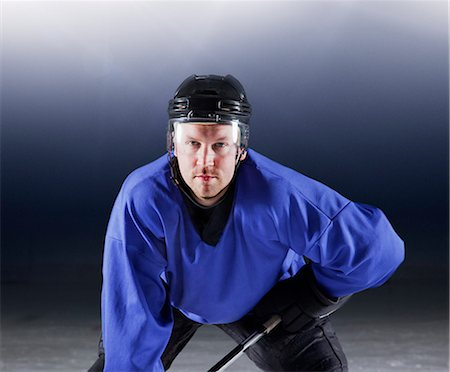 Portrait determined hockey player in blue uniform on ice Stock Photo - Premium Royalty-Free, Code: 6113-08698163