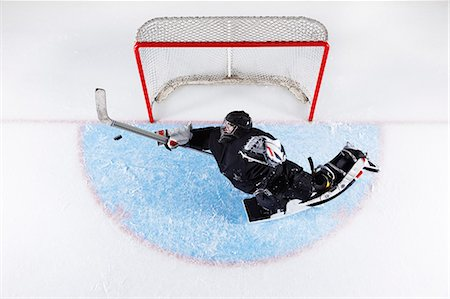 Overhead view hockey goalie reaching to block puck at goal net Stock Photo - Premium Royalty-Free, Code: 6113-08698161