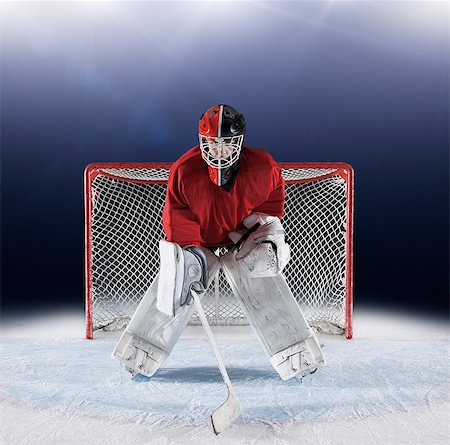 Portrait determined hockey goalie protecting goal net on ice Stock Photo - Premium Royalty-Free, Code: 6113-08698172