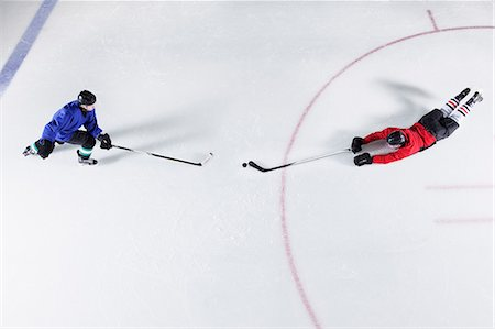 Overhead view hockey players diving for puck on ice Stock Photo - Premium Royalty-Free, Code: 6113-08698187