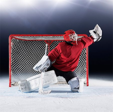 Hockey goalie in red uniform reaching for puck with glove at goal net Stock Photo - Premium Royalty-Free, Code: 6113-08698186