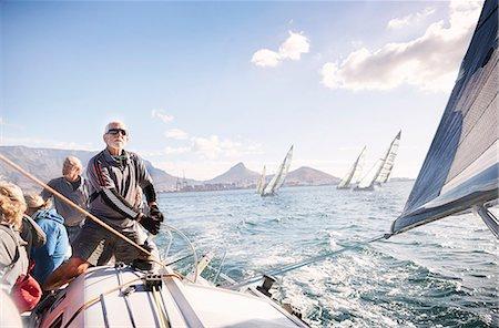 sailboat  ocean - Man adjusting sailboat rigging on sunny ocean Stock Photo - Premium Royalty-Free, Code: 6113-08698110