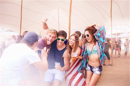 Playful young friends with beer posing for camera phone at music festival Stock Photo - Premium Royalty-Free, Code: 6113-08698269