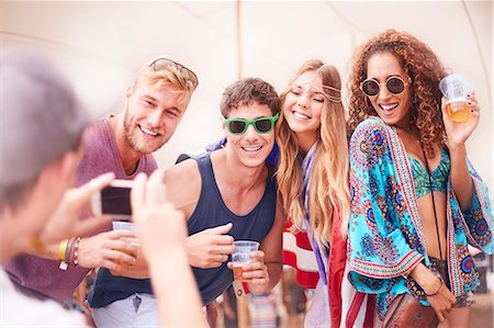 Young friends with beer posing for camera phone at music festival Stock Photo - Premium Royalty-Free, Code: 6113-08698272