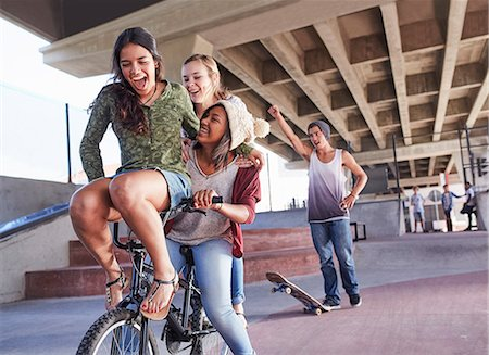Playful teenage friends riding BMX bicycle and skateboarding at skate park Stock Photo - Premium Royalty-Free, Code: 6113-08698208