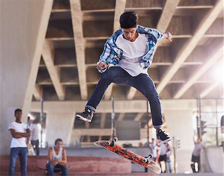 Friends watching teenage boy flipping skateboard at skate park Stock Photo - Premium Royalty-Free, Code: 6113-08698231