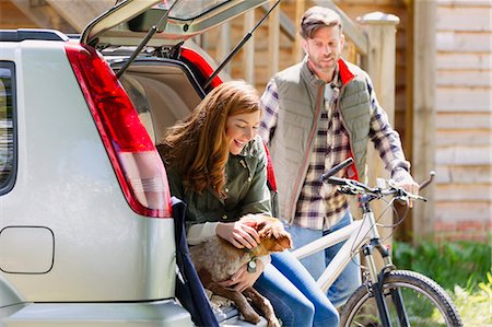 Couple with dog and mountain bike at back of car outside cabin Stock Photo - Premium Royalty-Free, Code: 6113-08743493