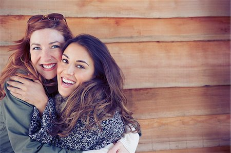 Portrait enthusiastic smiling female friends hugging outside cabin Stock Photo - Premium Royalty-Free, Code: 6113-08743550