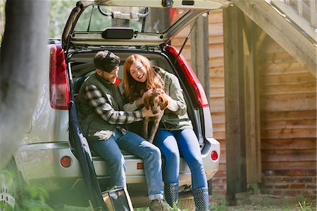 Couple petting dog at back of car outside sunny cabin Stock Photo - Premium Royalty-Free, Code: 6113-08743526