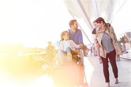 pushing - Family walking with luggage cart outside airport Stock Photo - Premium Royalty-Free, Code: 6113-08784140