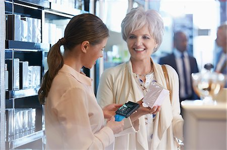 Woman buying perfume in shop from clerk with wireless credit card reader Stock Photo - Premium Royalty-Free, Code: 6113-08784124