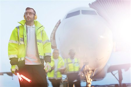 Air traffic controller standing in front of airplane on airport tarmac Stock Photo - Premium Royalty-Free, Code: 6113-08784243