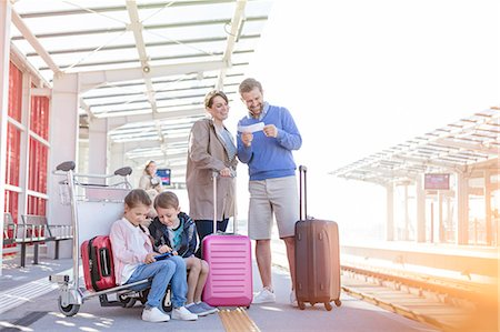 Family with suitcases waiting at train station platform Stock Photo - Premium Royalty-Free, Code: 6113-08784255