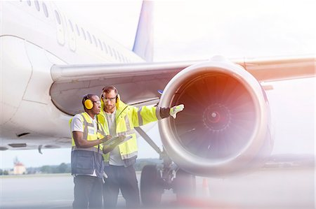 Air traffic control ground crew workers talking near airplane on airport tarmac Stock Photo - Premium Royalty-Free, Code: 6113-08784277